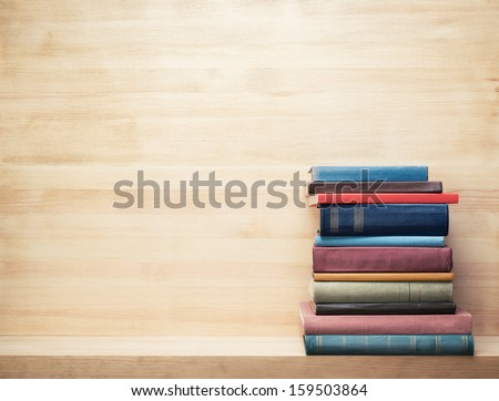Photo of  Old books on a wooden shelf.