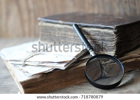 Old books on a wooden table and glass magnifier #718780879