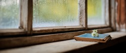 old books on the background of the village wooden wet window, copy space. autumn cold rainy days. The concept of Hygge, autumn mood.