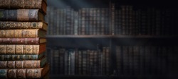 Old books on wooden shelf and ray of light. Bookshelf history theme grunge background. Concept on the theme of history, nostalgia, old age. Retro style.