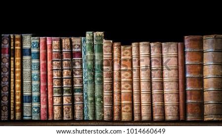 Old books on wooden shelf. Tiled Bookshelf background.