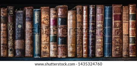 Old books on wooden shelf. Tiled Bookshelf background.  Concept on the theme of history, nostalgia, old age. Retro style. Stockfoto ©