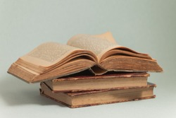 old books, open aged book, ancient paper pages, blurred text, blue background