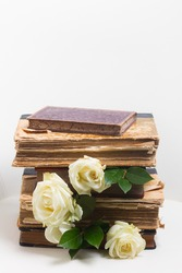 Old books pile with white flowers flowers on white chair background with copy space
