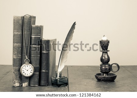 Old books, quill and inkwell, pocket watch, candlestick on wooden table