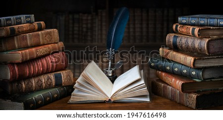 Old books ,quill pen and vintage inkwell on wooden desk in old library. Ancient books historical background. Retro style. Conceptual background on history, education, literature topics.