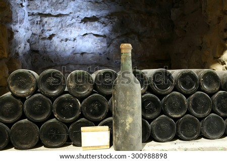 Old bottle of wine in the cellar of the winery\Ancient wine bottles in the cellar\Winery\Red wine of ancient times