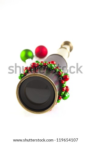 old brass and leather telescope with red and green christmas decorations isolated on white vertical