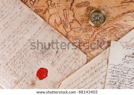 Old brass compass lying on a very old map and ancient documents