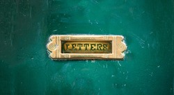 Old brass mail letter box on a green front door, text letters