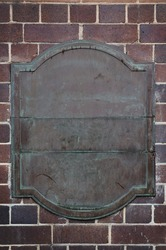 Old brass plaque on a brick wall