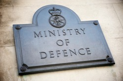 Old brass sign marking the offices of the British Ministry of Defence on a building in Whitehall, London, UK