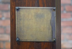 Old brass yellow metal plate frame and wooden pillar on brick wall background