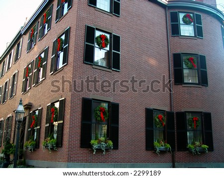 old brick apartment building with shutters is adorned with christmas wreaths in every window