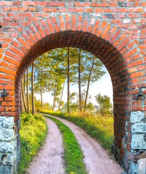 Old brick arch with entrance to the countryside road among pine forest