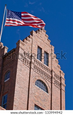 Old brick building, in a historic part of town, flying the American flag