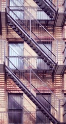 Old brick building with iron fire escape, color toning applied, New York City, USA.