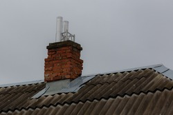 Old brick chimney on a residential building. Red brick chimney.