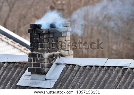 Old brick chimney on old house roof