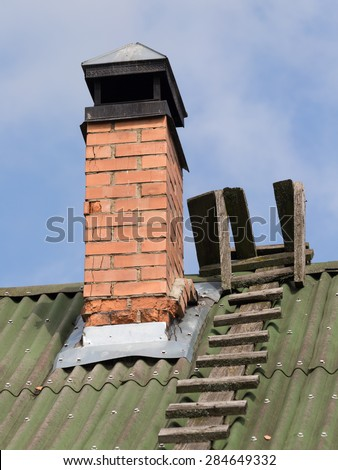 Old brick chimney with a headroom of stainless steel and wooden lnestnitsa on the green roof