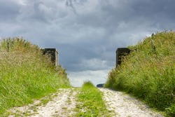 Old brick gate in a dike overgrown with saturated green grass under a dark stormy sky. Concept of portal, gateway or path to the unknown or eternity. Image with copy space.