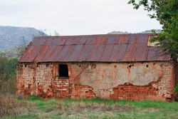 OLD BRICK HOUSE WITH FLAKING PLASTER IN DISREPAIR