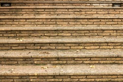 Old brick staircase with fallen leaves after the rain.
