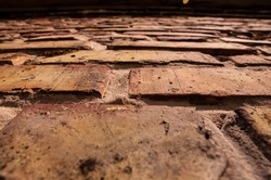 Old brick texture. Fully filled image of a building facade with damaged stucco. Background of an old brick wall
