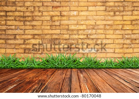 Old brick wall and green grass on wood floor