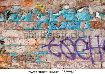 Old brick wall in abandoned building, with peeling paint and graffiti