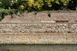 Old brick wall quay mirrored in the water of the river Jeker in Tongeren, Belgium. The Roman city wall dates back to the fourth century AD