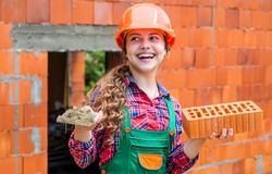 Old brick wall repair. kid wear helmet on construction site. teen girl builder with building brick. bricklayer child on repairing work. concept of renovation in workshop. busy professional carpenter