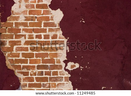Old brick wall showing through broken plaster