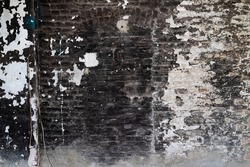Old brick wall with black and white peeled off paint and soot and grime in a ruined factory in a lost place in Germany