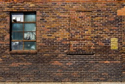 Old brick wall with brick filled window.