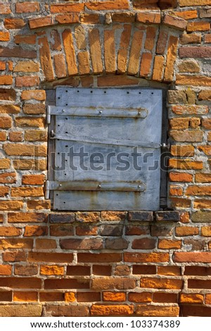Old brick wall with closed steel door