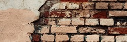Old brick wall with peeling stucco. Weathered rough wall surface with brickwork. The wall is painted in different colors. Wide panoramic texture for background and design.