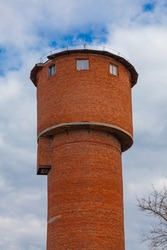 Old brick water tower against cloudy sky background