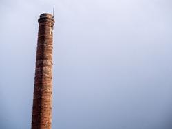 Old bricks factory chimney with bricks. blue sky background.