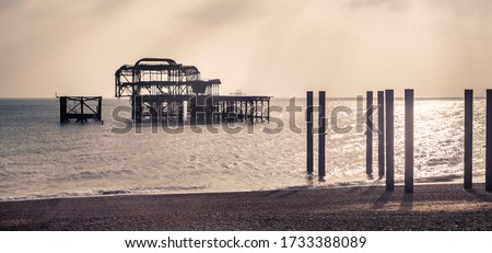 Old Brighton West Pier, at Brighton Beach, in Brighton, UK. Empty an cold weather. Orange cloudy light. No person.