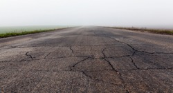 old broken asphalt road, photographed close-up in a misty morning. bad visibility. Grey Sky. On the road there are visible broken asphalt, cracks