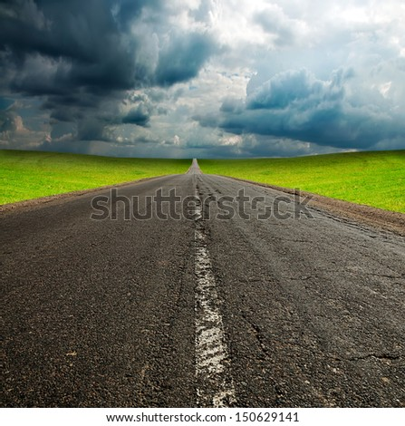 old broken asphault road in green field over blue cloudy sky