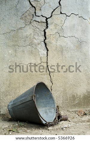 Old broken bucket in front of cracked wall of well