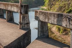 Old broken concrete bridge collapsed until they split apart. Harm to commuters.