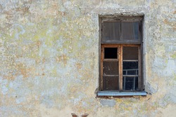 Old broken dirty window on an old wall with cracked plaster and peeling paint. From the window of the world series.