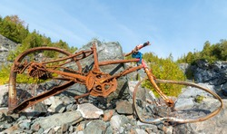 Old broken rusted bicycle in a rock quarry. The bicycle is bent and severely damaged, and parts are missing. The spokes are broken. A chain lock is still wrapped under the handle bars.