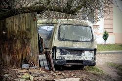 Old broken rusty van in yard near wooden building under leafless tree