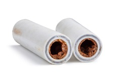 Old broken sludge plumbing polypropylene pipes with red rust and limescale. Corrosion, sludge and hard water concept. Obsolete pipes isolated on white background
