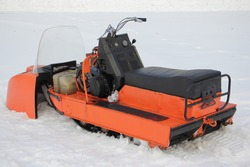 Old broken Soviet utility snowmobile without cover close up - seat, teering, engine handle and fuel tank on white snow at winter day