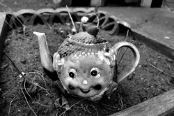 old broken teapot with a childish face, a long-lost toy that looks scary